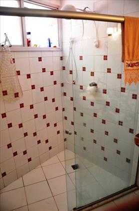 Banheiro social decorado e com box de vidro.
