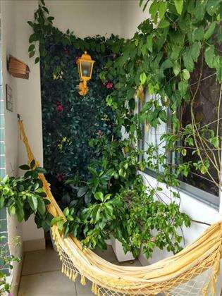 Um cantinho com rede na varanda para relaxar
