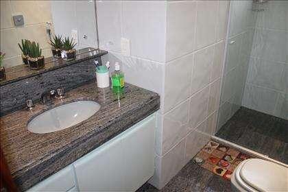 Banho social com banda em granito e armário.