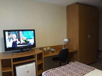 Banca de escritório, TV e frigobar.