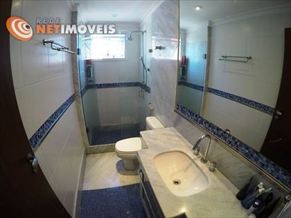 Banheiro social com piso em vidrotil e mármore e paredes em porcelanato com detalhes em vidrotil.