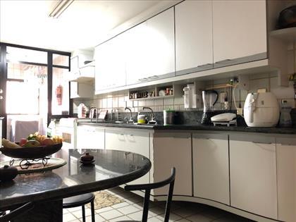 Cozinha separada da área com porta de vidro.