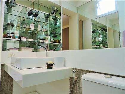 Banheiro da suíte com prateleiras de vidro