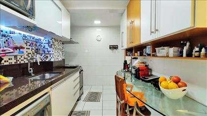 Cozinha com bancada, armários e iluminação