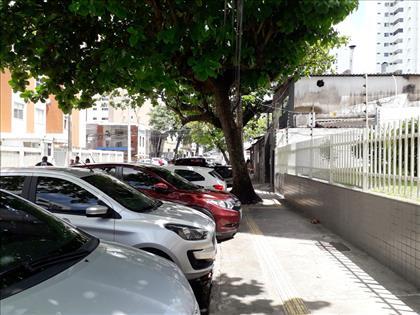 vista rua com estacionamento porta do prédio